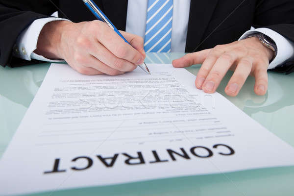 Businessman Signing Contract Paper At Office Desk Stock photo © AndreyPopov