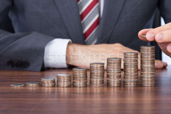 Businessman Stacking Coins In Increasing Order At Desk Stock photo © AndreyPopov
