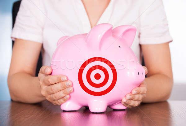 Businesswoman Holding Piggybank With Bulls Eye Target Stock photo © AndreyPopov