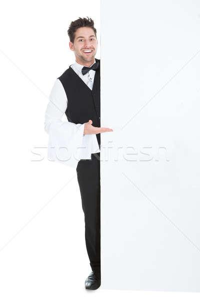 Butler naar billboard jonge geïsoleerd witte Stockfoto © AndreyPopov