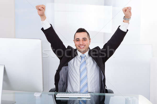 Businessman With Arms Raised Sitting At Computer Desk Stock photo © AndreyPopov