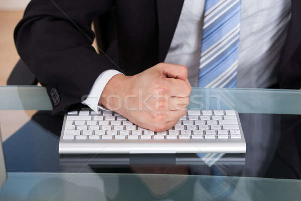 Stock photo: Midsection of businessman pounding fist on keyboard
