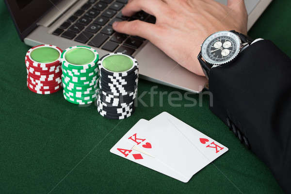 Stock photo: Businessman Using Laptop By Stacked Poker Chips And Cards