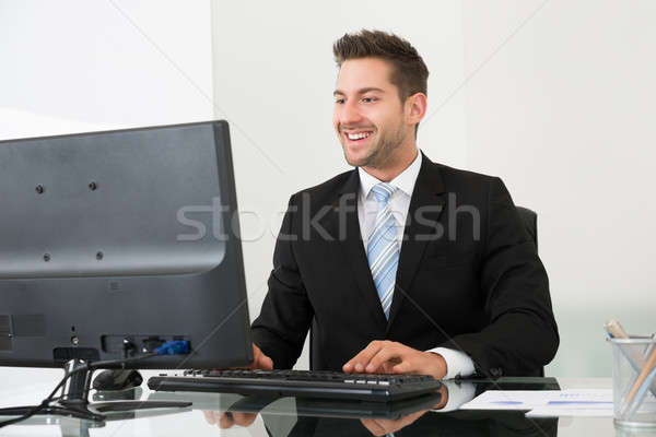 Businessman Using Computer At Desk Stock photo © AndreyPopov