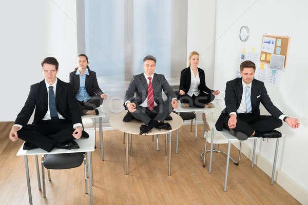 Meditating Businesspeople Sitting On Desk Stock photo © AndreyPopov