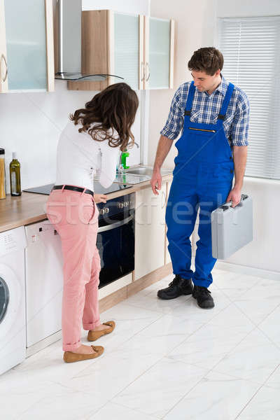 Housewife Showing Damaged Oven To Worker Stock photo © AndreyPopov