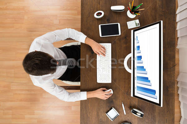 Businessperson Analyzing Statistical Graph On Computer Stock photo © AndreyPopov