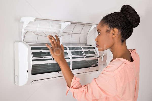 Mujer apertura acondicionador de aire jóvenes África casa Foto stock © AndreyPopov