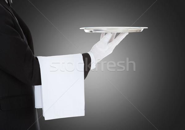 Waiter Holding Empty Silver Tray Over Gray Background Stock photo © AndreyPopov