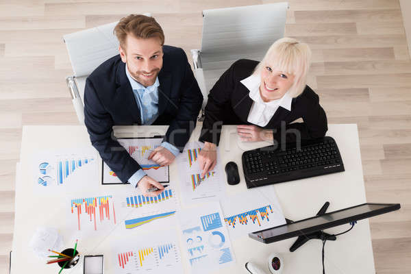 Two Young Businesspeople Analyzing Financial Graphs Stock photo © AndreyPopov
