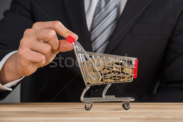 Businessman Carrying Coin In Shopping Trolley Stock photo © AndreyPopov