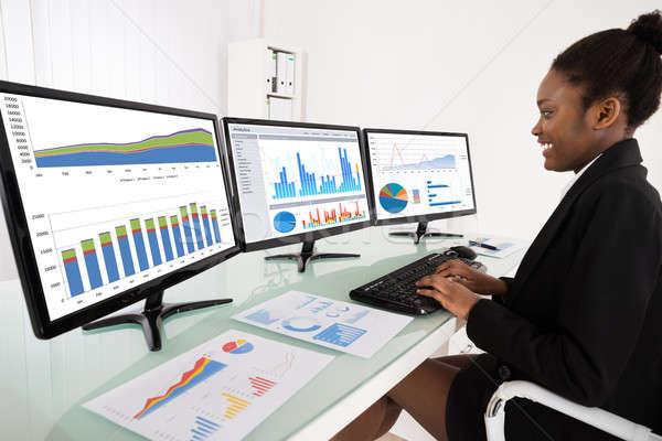 Femme d'affaires graphique multiple ordinateur jeunes africaine Photo stock © AndreyPopov