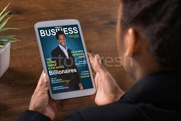 Businesswoman Reading Online Magazine On Digital Tablet Stock photo © AndreyPopov