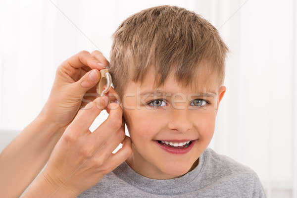 Close-up Of A Smiling Boy With Hearing Aid Stock photo © AndreyPopov