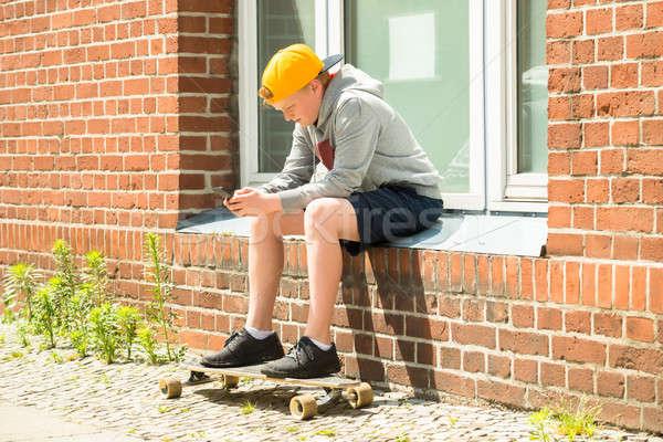 мальчика скейтборде мобильного телефона сидят за пределами телефон Сток-фото © AndreyPopov