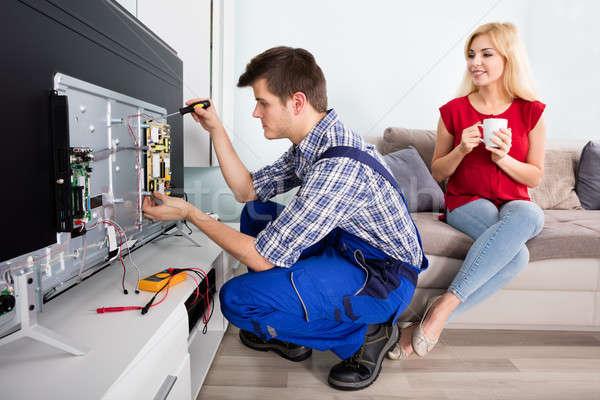 Nő néz technikus javít televízió fiatal nő Stock fotó © AndreyPopov