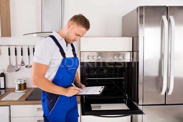 Male Technician Writing On Clipboard In Kitchen Stock photo © AndreyPopov