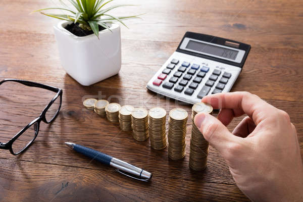 Person Doing Calculation With Stacked Coins Stock photo © AndreyPopov