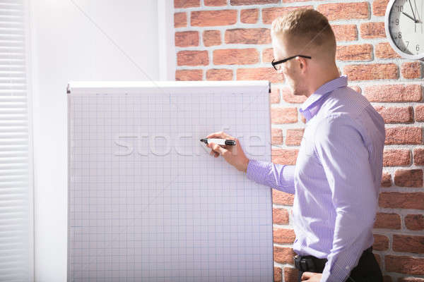 Businessman Writing On Grid Flip Chart Stock photo © AndreyPopov