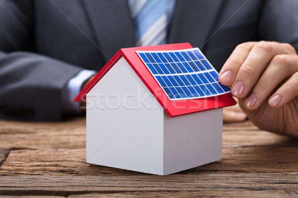 Businessman Sticking Solar Panel On Model Home Stock photo © AndreyPopov