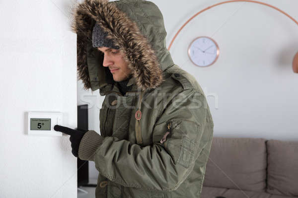 Man In Warm Clothing Pointing To Current Room Temperature Stock photo © AndreyPopov