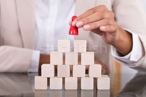 Businesswoman Placing Red Figure On Arranged Blocks Stock photo © AndreyPopov