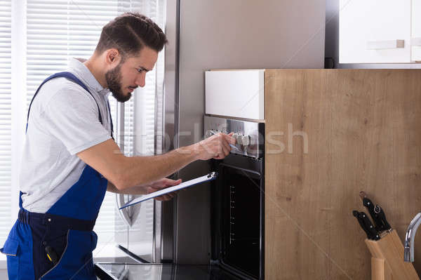 Electrician Writing On Clipboard In Front Of Oven Stock photo © AndreyPopov