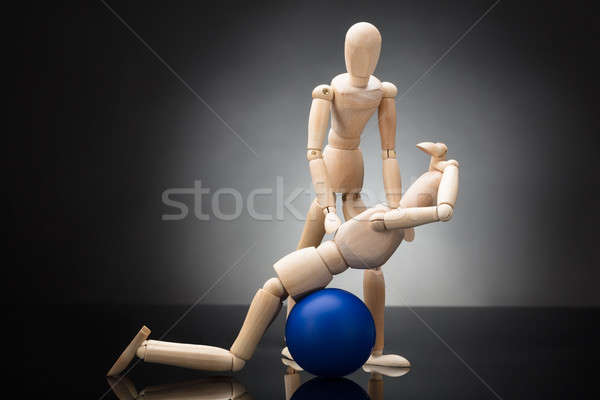 Trainer Assisting Wooden Figurine Exercising On Fitness Ball Stock photo © AndreyPopov