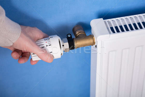 Person Adjusting Temperature Of Radiator Thermostat Stock photo © AndreyPopov