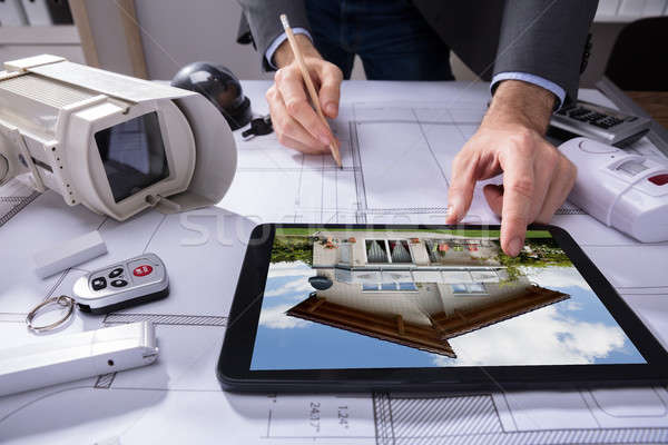 Architect Using Digital Tablet While Drawing Plan On Blueprint Stock photo © AndreyPopov