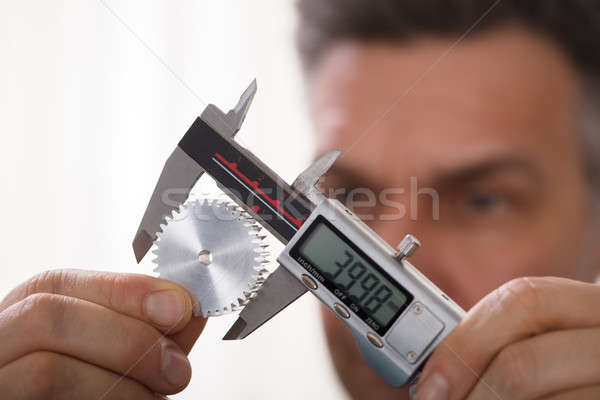 Man Measuring Size Of Gear With Digital Vernier Caliper Stock photo © AndreyPopov