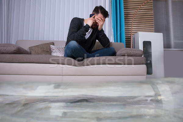 Man Sitting On Sofa Calling To Plumber Stock photo © AndreyPopov