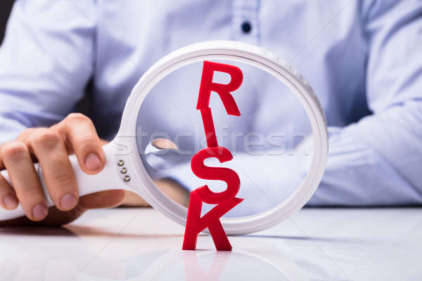 Hand Examining Risk Word With Help Of Magnifying Glass Stock photo © AndreyPopov