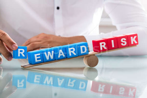 Businessman showing unbalance between reward and risk Stock photo © AndreyPopov
