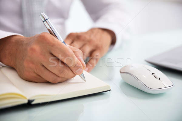 Businessperson Writing Schedule In Diary With Pen Stock photo © AndreyPopov