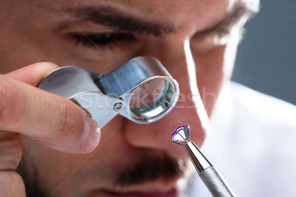 Jeweler Looking At Diamond Through Magnifying Loupe Stock photo © AndreyPopov