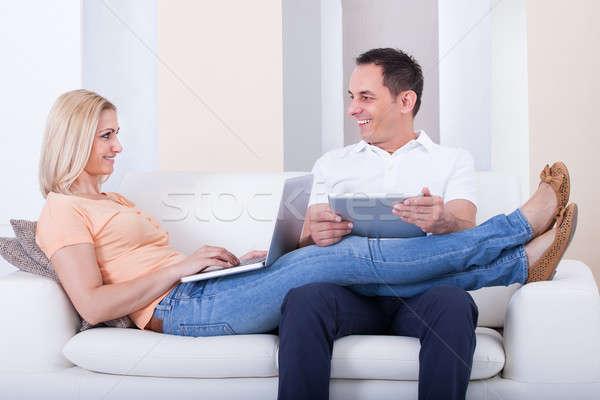 Happy Mid-adult Couple Using Digital Gadgets Stock photo © AndreyPopov