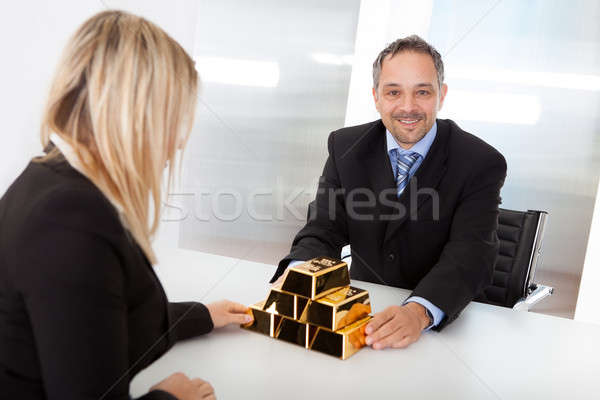 Businessman receiving gold bars Stock photo © AndreyPopov