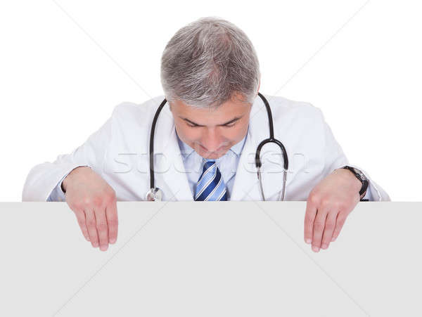 Stock photo: Portrait Of Male Doctor Holding Placard