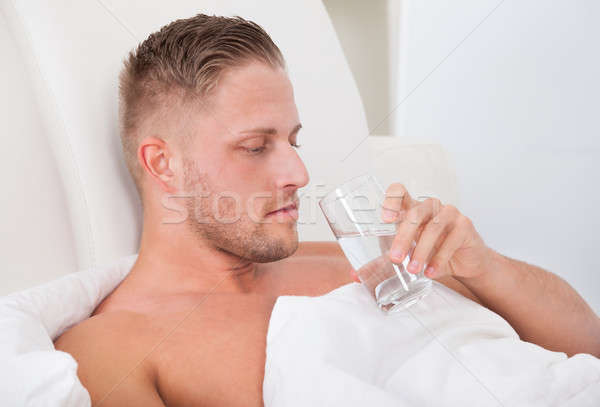 Man drinking a glass of water in bed Stock photo © AndreyPopov