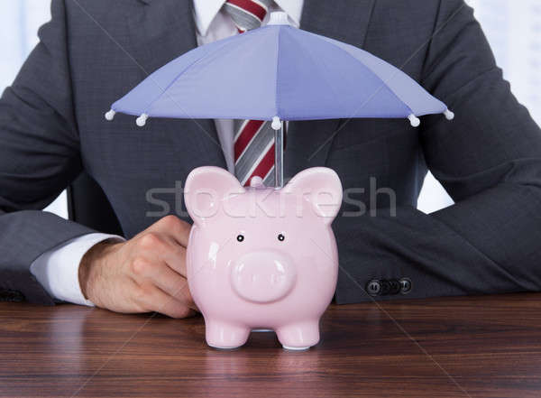 Businessman Sheltering Piggybank With Umbrella At Desk Stock photo © AndreyPopov