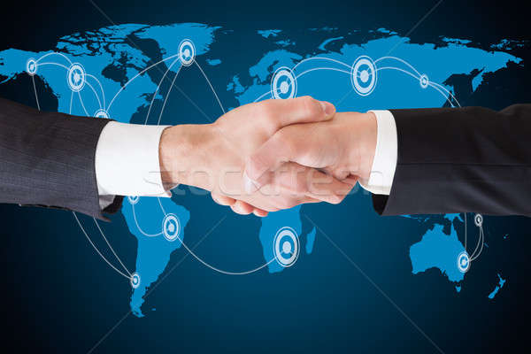Businessmen Shaking Hands Against World Map Stock photo © AndreyPopov