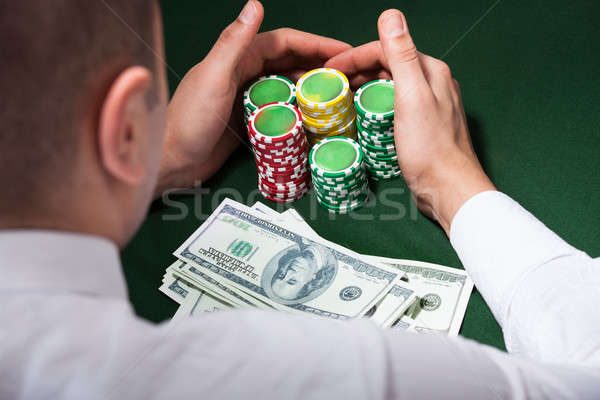 Man Scooping Up Dollars And Poker Chips Stock photo © AndreyPopov