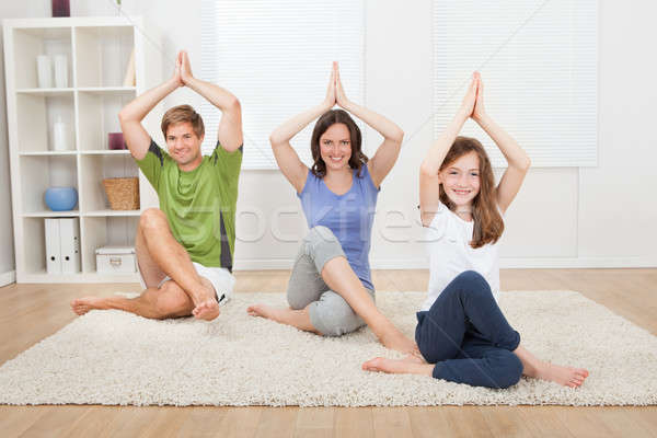 Smiling Family Practicing Yoga On Rug Stock photo © AndreyPopov