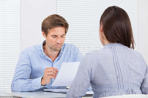 Businessman Checking Resume Of Female Candidate During Meeting Stock photo © AndreyPopov