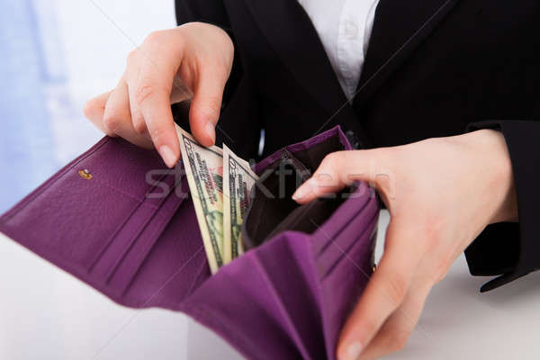 Businesswoman Putting American Banknotes In Wallet Stock photo © AndreyPopov