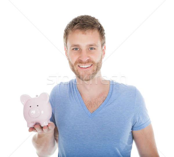 Man Holding Piggybank Over White Background Stock photo © AndreyPopov