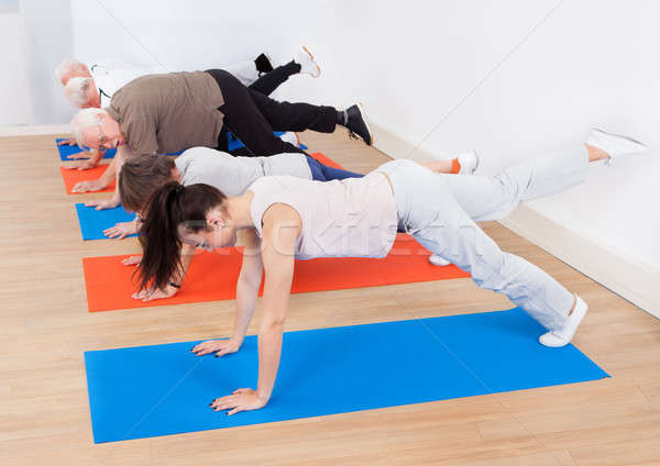 Trainer And Customers Doing Exercises Stock photo © AndreyPopov