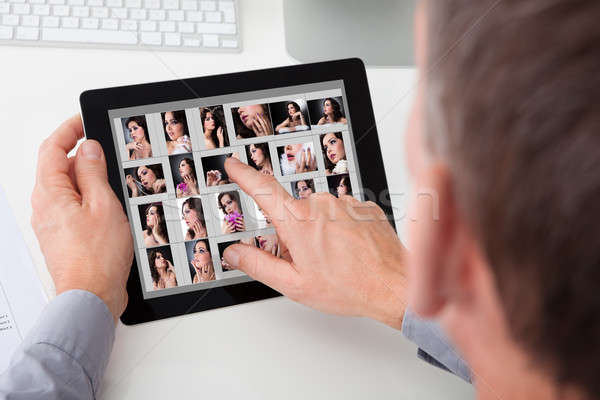 Man Browsing Pictures Of Young Woman On Digital Tablet Stock photo © AndreyPopov