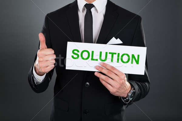 Businessman Gesturing Thumbsup While Holding Solution Sign Stock photo © AndreyPopov